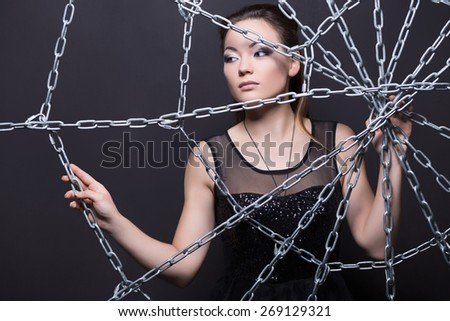 Portrait of thoughtful brunette posing behind the web of chains - stock photo
