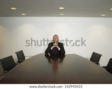Portrait of thoughtful businessman with hands clasped sitting alone in conference room - stock photo