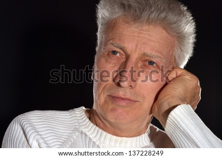 Portrait of thoughtful elderly man on a black background