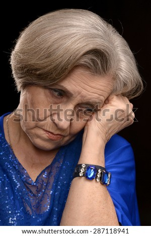 portrait of thoughtful elderly woman in white on a black background
