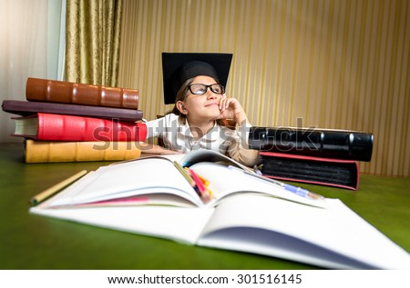Portrait of thoughtful girl in graduation cap dreaming while sitting at table - stock photo