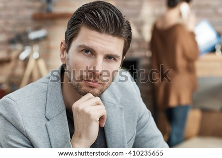 Portrait of thoughtful handsome businessman sitting with hand on chin. - stock photo