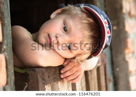 Portrait of thoughtful little boy. outdoors - stock photo