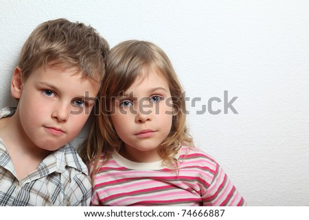 Portrait of thoughtful little girl and boy, they put heads on each other - stock photo