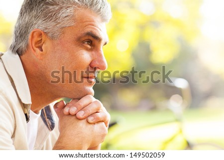 portrait of thoughtful middle aged man outdoors - stock photo