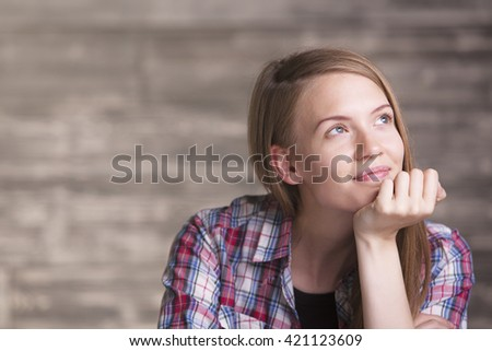 Portrait of thoughtful smiling young woman in casual shirt - stock photo