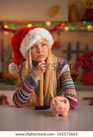 Portrait of thoughtful teenage girl in santa hat with hammer and piggy bank in christmas decorated kitchen - stock photo