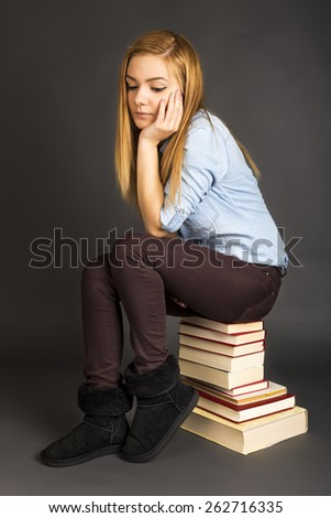 Portrait of thoughtful teenage girl sitting on pile of books over gray background - stock photo