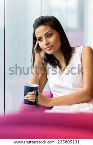 portrait of thoughtful woman sitting in coffee shop - stock photo