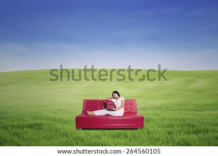 Portrait of thoughtful woman using laptop on sofa. Shot outdoor - stock photo