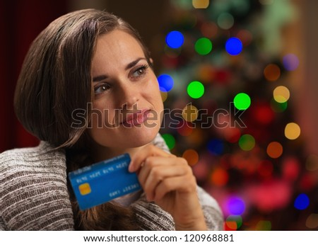 Portrait of thoughtful woman with credit card in front of Christmas lights - stock photo