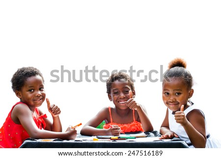 Portrait of three African girls doing leisure activity and thumbs up at table.Isolated on white background.