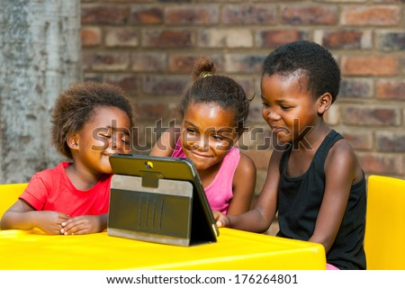 Portrait of three African girls playing leisure games on tablet. - stock photo