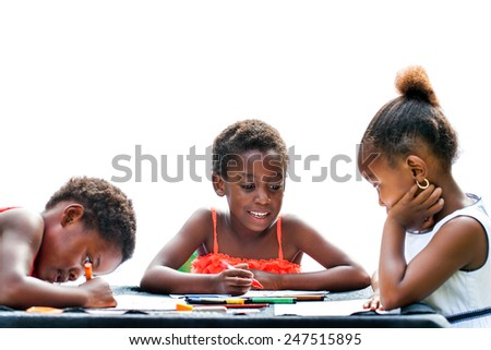 Portrait of three African kids drawing together with crayons at desk.Isolated on white background.