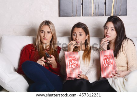 Portrait of three and beautiful young friends eating popcorn and watching movies. Indoors. - stock photo
