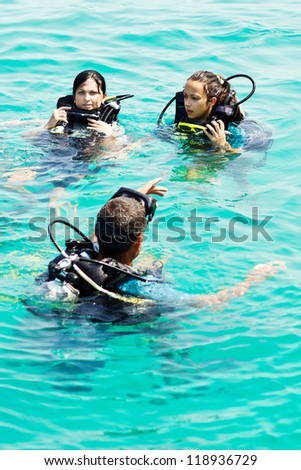 Portrait of three attractive friends going scuba diving - stock photo