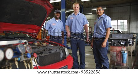 Portrait of three auto shop mechanics - stock photo