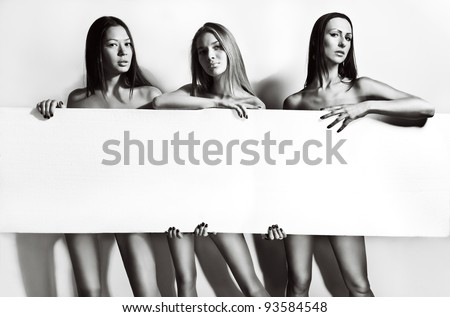 Portrait of three beautiful and sexy women holding a blank posing on white background - stock photo