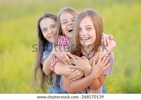 portrait of three beautiful girlfriends on the nature - stock photo