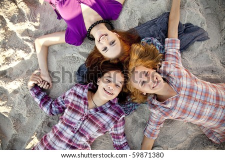 Portrait of three beautiful girls on sand.