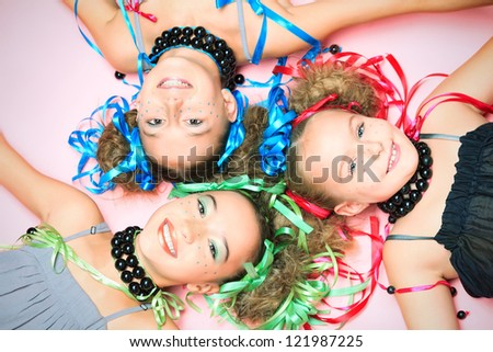 Portrait of three beautiful girls with festive make-up, hairstyle and dress. - stock photo