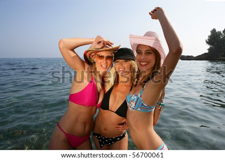 Portrait of three beautiful women bathing in the sea - stock photo