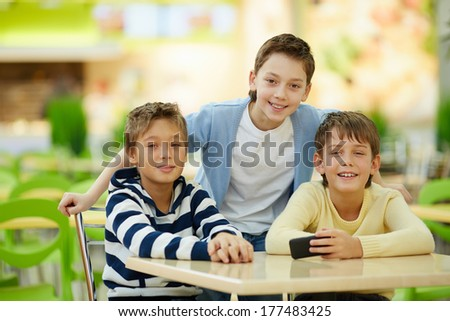 Portrait of three boyfriends at cafe table - stock photo