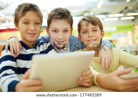 Portrait of three boys sitting in cafe - stock photo