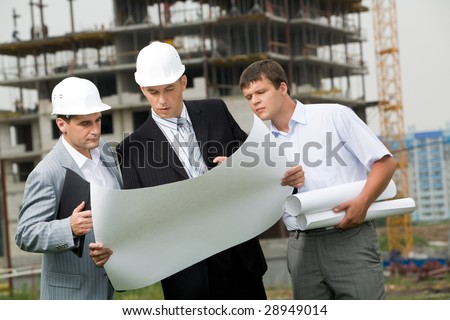 Portrait of three builders looking at new project and discussing it outside - stock photo