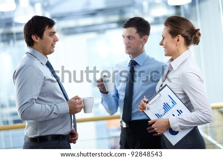 Portrait of three business partners sharing working plans and ideas - stock photo