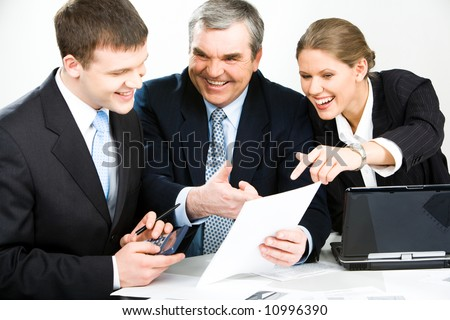 Portrait of three business people discussing a working document - stock photo
