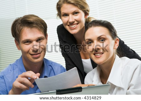 Portrait of three business people looking at camera in a working environment