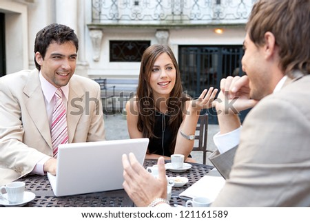 Portrait of three business people sharing a table at a coffee shop terrace, having a meeting and talking while using technology in the financial city district. - stock photo