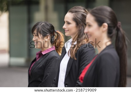 Portrait of three business women. Focus is on asian woman at the end. Interracial group of business women. - stock photo