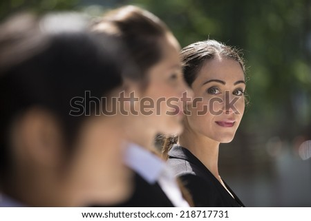 Portrait of three business women. Shallow depth-of-field/focus used to highlight the caucasian woman at the end of row.  Interracial group of business women. - stock photo