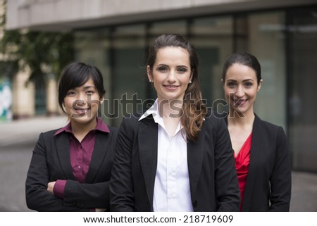 Portrait of three business women. Shallow depth-of-field, focus used to highlight the woman in the middle. Interracial group of business women. - stock photo