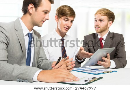 portrait of three businessmen discussing new plan at office