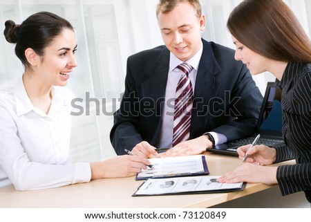 Portrait of three businesspeople discussing plan at meeting - stock photo