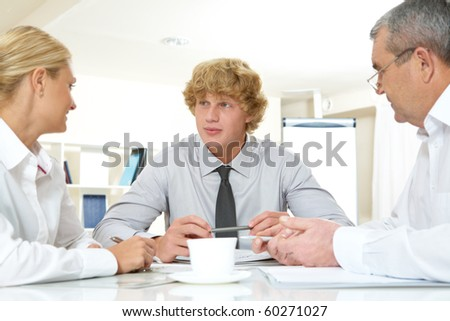 Portrait of three businesspeople interacting at meeting - stock photo