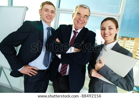 Portrait of three businesspeople looking at camera and smiling - stock photo