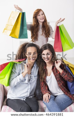 Portrait of three cheerful teenagers with lots of paper shopping bags, smiling at the camera
