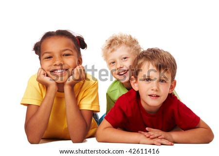 Portrait of three children lying and looking at camera - stock photo