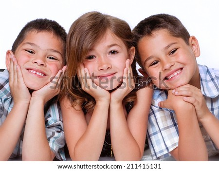 Portrait of three children, two boys and a girl aged between 5 and 8 isolated against white background - stock photo