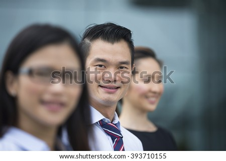Portrait of three Chinese business colleagues in a modern urban setting.  Focus is on the man in the middle.