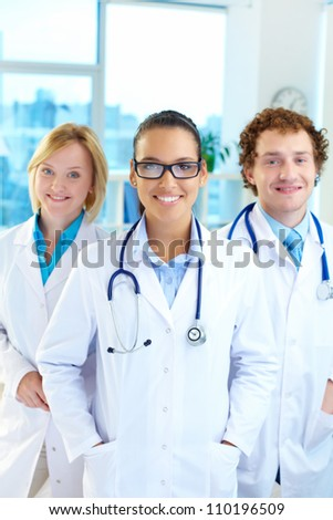 Portrait of three clinicians in white coats looking at camera with smiling brunette in front - stock photo
