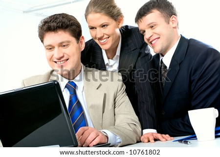Portrait of three confident business partners looking at the laptop monitor in the office with smiles with pen, cup and folder near by