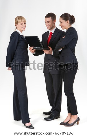 Portrait of three confident business partners standing next to each other and looking at laptop screen