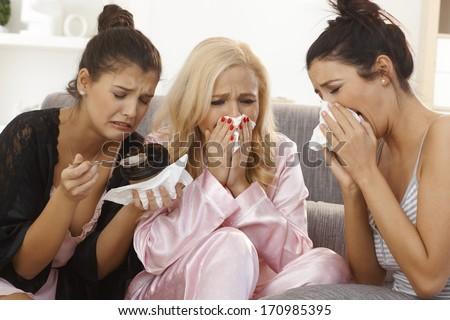 Portrait of three crying women at home, sharing sorrow, wearing pyjamas. - stock photo