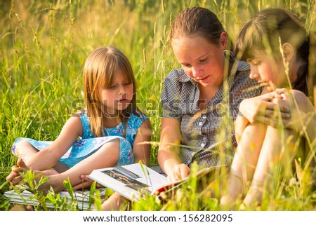 Portrait of three cute little girls reading book in natural environment together. - stock photo