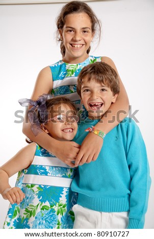 Portrait of three cute young siblings with matching clothes - stock photo